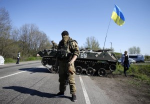 A Ukrainian soldier stands guard in front of an armoured personnel carrier at a checkpoint in the village of Malinivka, east of Slaviansk