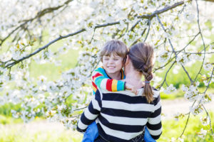 Young mum and her little son, blond child hugging in blooming cherry garden in spring. Happy family celebrating mother's day.